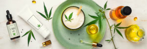 Cosmetics with cannabis oil on a turquoise plate on a light marble background