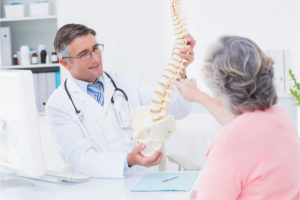 doctor and patient examining spine model